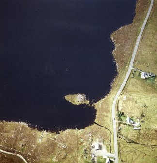 Oblique aerial view centred on remains of the broch with the possible crannog adjacent, taken from the ENE.
