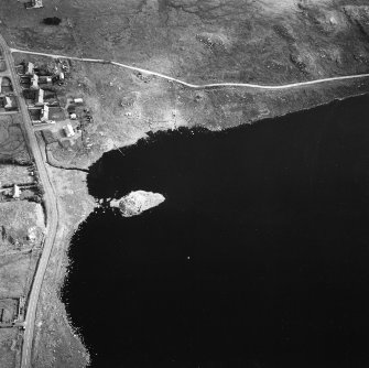 Oblique aerial view centred on remains of the broch with the possible crannog adjacent, taken from the W.