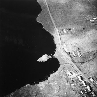 Oblique aerial view centred on remains of the broch with the possible crannog adjacent, taken from the ESE.