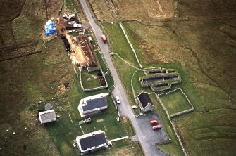 Oblique aerial view centred on the re-roofing of the museum with the remains of the blackhouse adjacent, taken from the N.