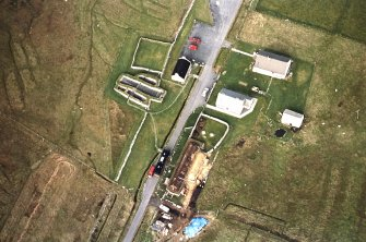 Oblique aerial view centred on the re-roofing of the museum with the remains of the blackhouse adjacent, taken from the SE.