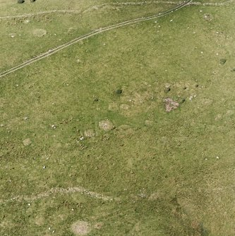 Oblique aerial view of Garbeg centred on the remains of square and round barrows in an area of hut-circles, small cairns and a field-system, taken from the SE.