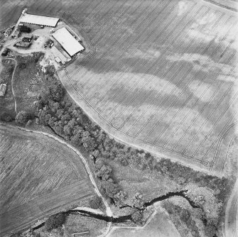 Leadketty, oblique aerial view, taken from the SE, centred on the cropmark of an enclosure. An alignment of pits running from it towards the top right-hand corner of the photograph is part of a large pit-defined enclosure.