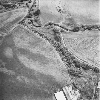 Leadketty, oblique aerial view, taken from the WNW, centred on the cropmark of an enclosure. An alignment of pits in the centre left of the photograph is part of a large pit-defined enclosure.
