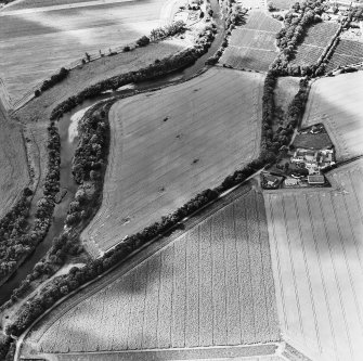 Oblique aerial view centred on the site of a pit-defined cursus and enclosure, taken from the NE.
