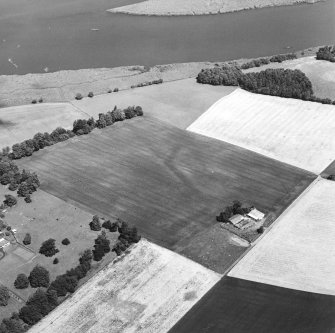 Oblique aerial view centred on the cropmarks of the E and S ditches of the Roman Fortress, with the farmsteading adjacent, taken from the SSW.