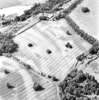 Rossie Priory, oblique aerial view, taken from the ESE, centred on a field containing the cropmarks of an unenclosed settlement to the right, and barrows to the left.