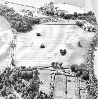 Rossie Priory, oblique aerial view, taken from the NE, centred on a field containing the cropmarks of an unenclosed settlement to the right, and barrows to the left.