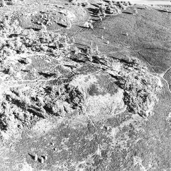 Oblique aerial view centred on the remains of the fort and possible cairn, taken from the SW.