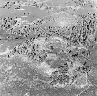 Oblique aerial view centred on the remains of the fort and possible cairn, taken from the S.