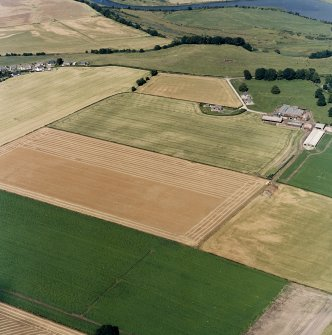 General oblique aerial view centred on the cropmarks of the cursus monuments, and the barrows, pits and rig with the farmsteading adjacent, taken from the SSW.