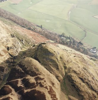 Oblique aerial view of Dumyat centred on the remains of a fort and cairn, taken from the NW.