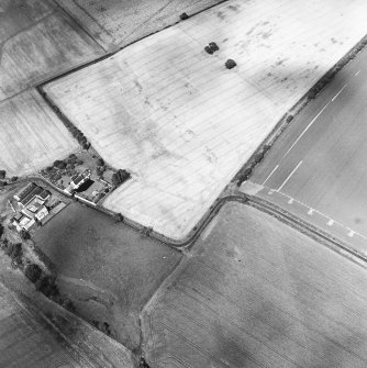 Oblique aerial view centred on the cropmarks of the field boundaries and further cropmarks with farmhouse adjacent, taken from the SSW.