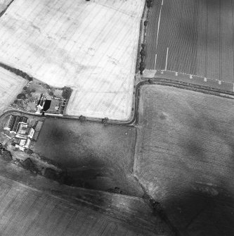Oblique aerial view centred on the cropmarks of the field boundaries and further cropmarks with farmhouse adjacent, taken from the SW.