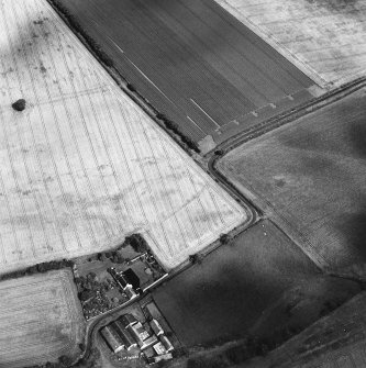 Oblique aerial view centred on the cropmarks of the field boundaries and further cropmarks with farmhouse adjacent, taken from the W.