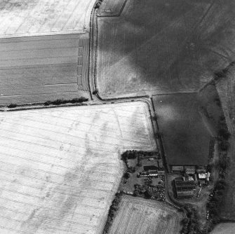Oblique aerial view centred on the cropmarks of the field boundaries and further cropmarks with farmhouse adjacent, taken from the NW.