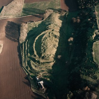 Oblique aerial view centred on the remains of the fort with farmsteading adjacent, taken from the WSW.