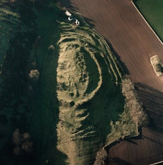 Oblique aerial view centred on the remains of the fort with farmsteading adjacent, taken from the E.