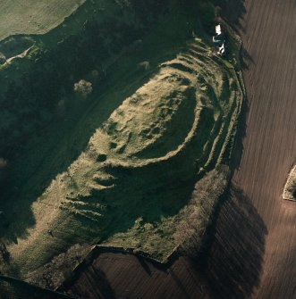 Oblique aerial view centred on the remains of the fort with farmsteading adjacent, taken from the NE.