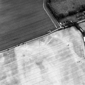 Phantassie, oblique aerial view, taken from the W, centred on the cropmarks of an enclosure and a possible building. A dovecot is visible in the centre of the photograph.