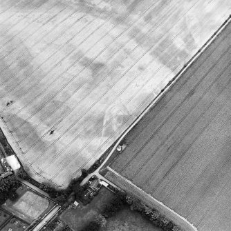 Phantassie, oblique aerial view, taken from the SE, centred on the cropmarks of an enclosure and a possible building. A dovecot is visible in the centre of the photograph.
