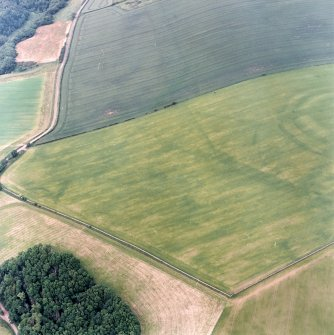 Oblique aerial view centred on the cropmarks of the field boundaries and cropmarks with fort adjacent, taken from the WSW.