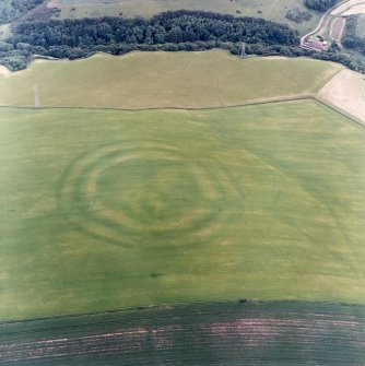 Oblique aerial view centred on the cropmarks of the fort with field boundaries and  cropmarks adjacent, taken from the NE.
