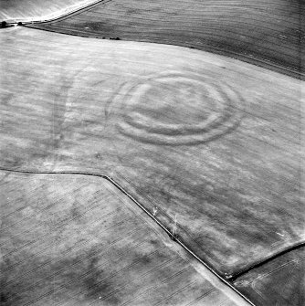 Oblique aerial view centred on the cropmarks of the fort with field boundaries and  cropmarks adjacent, taken from the SSW.