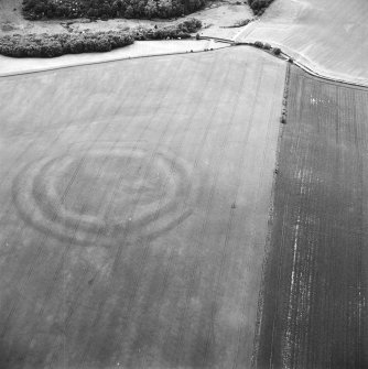 Oblique aerial view centred on the cropmarks of the fort with field boundaries and  cropmarks adjacent, taken from the ESE.