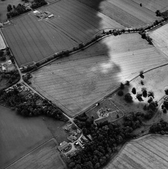 Oblique aerial view centred on the possible enclosures and linear cropmarks with the church, burial ground, manse, lodge, school, farmhouses, farmsteadings and cottages adjacent, taken from the NE.