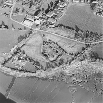 Oblique aerial view centred on the remains of the castle with Castle Mains house and school adjacent, taken from the W.