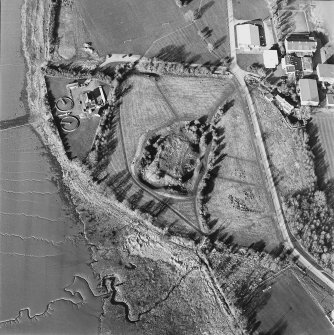 Oblique aerial view centred on the remains of the castle with Castle Mains house and school adjacent, taken from the SW.