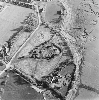 Oblique aerial view centred on the remains of the castle with Castle Mains house adjacent, taken from the NNW.