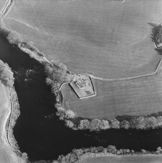 Oblique aerial view centred on the remains of the church and burial ground with the remains of a motte in trees adjacent, taken from the WNW.