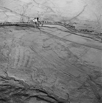 Oblique aerial view of Toft Knowes centred on the remains of a field-system, rig and pens with a farmstead and quarries and a settlement adjacent and a castle in the background, taken from the S.