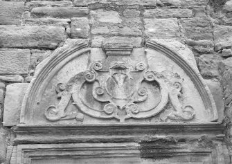 Detail of the broken pedimented doorway.
