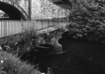 Detailed view from S of  two-arched former railway bridge beneath aqueduct, with the Luggie Water in the foreground