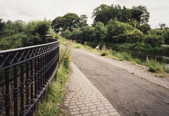 View from NE of the canal and tow-path, with iron railings (foreground left)