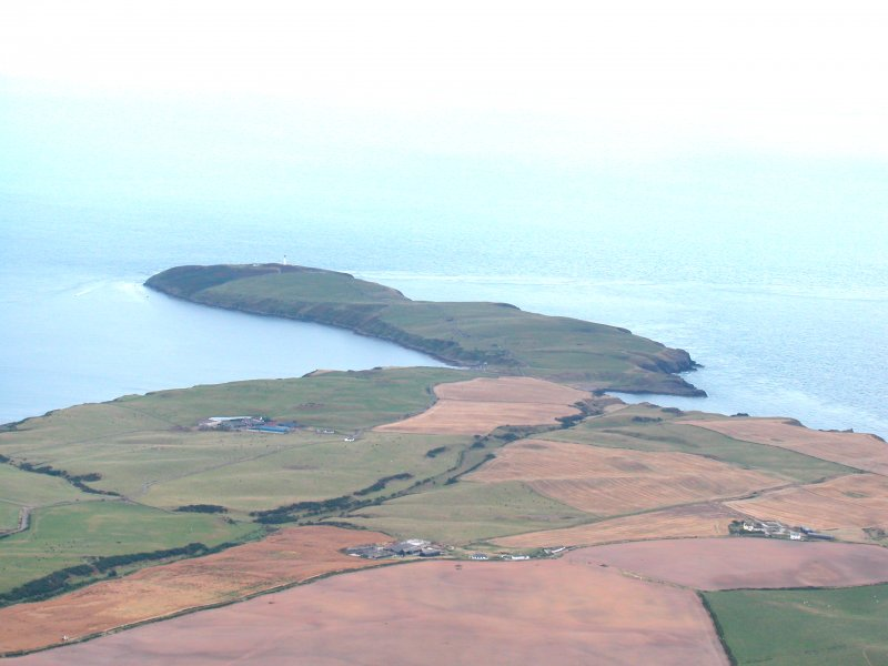 General oblique aerial view centred on the Mull of Galloway earthwork with the lighthouse in the distance, taken from the NNW.