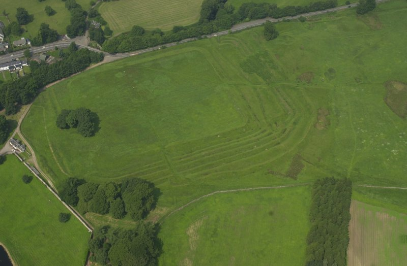 Oblique aerial view centred on the remains of the Roman Fort, chapel and burial ground, with road bridge adjacent, taken from the SE.