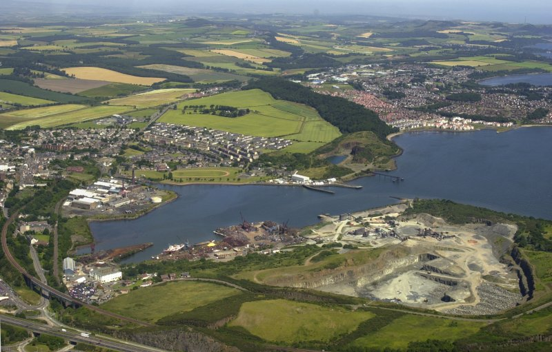 Oblique aerial view looking across Inner Bay with Inverkeithing, Dalgety Bay, quarry, paper mill, naval base mansions and pier adjacent, taken from the SW.