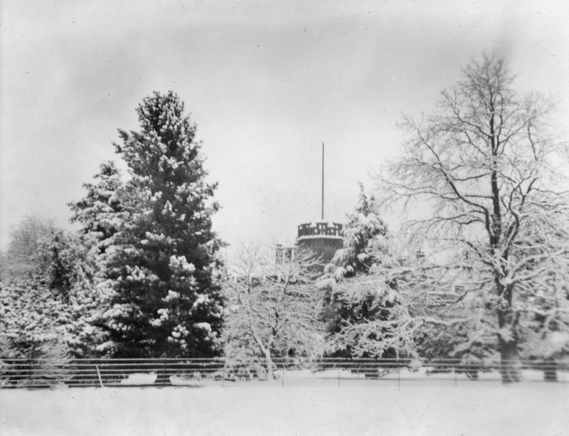 View of Inchrye Abbye tower beyond the trees in snow.