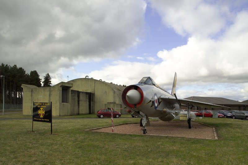 View.  Dispersal site showing Squadron gate guard, Lightning F3 and the rear of a hardened bombproof aircraft shelter from E.