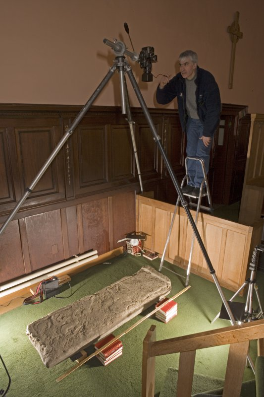 Interior view of Logierait Parish Church showing Mr S Wallace, RCAHMS, photographing Pictish cross slab