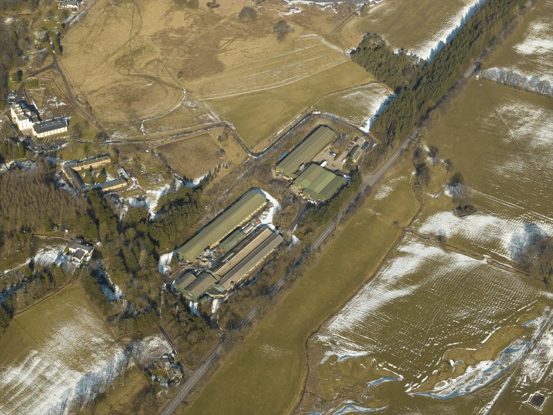 Oblique aerial view of the chicken sheds with the country house and  the remains of the gardens adjacent, taken from the S.
