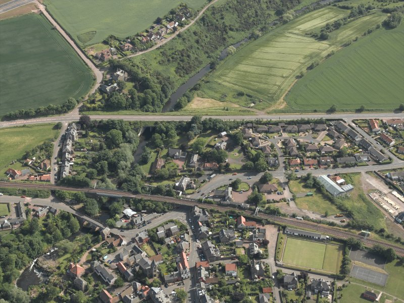 Oblique aerial view of the village centred on the road and rail bridges, taken from the N.