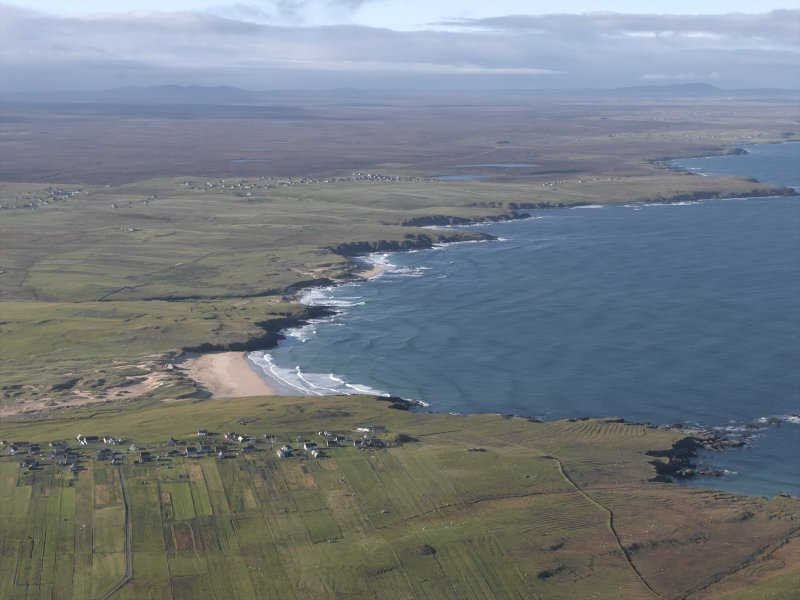 General oblique aerial view looking across the crofting township along the coastline, taken from the NE.