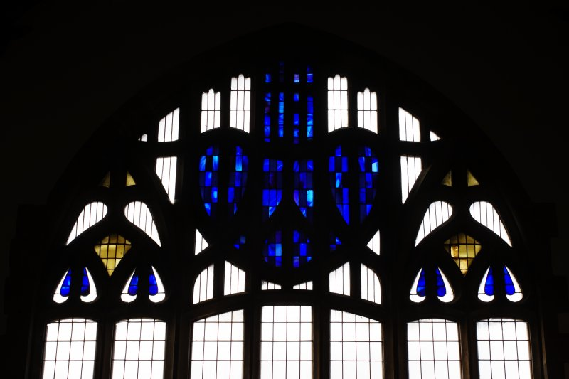 Interior view of Queen's Cross Church from the East showing detail of heart designed stained glass window.