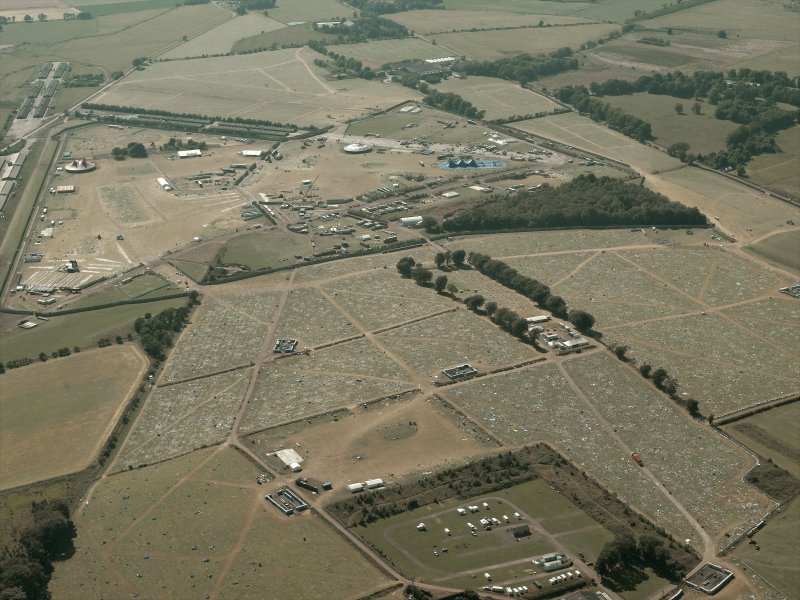 General oblique aerial view of the remains of the airfield and T in the Park, taken from the E.
