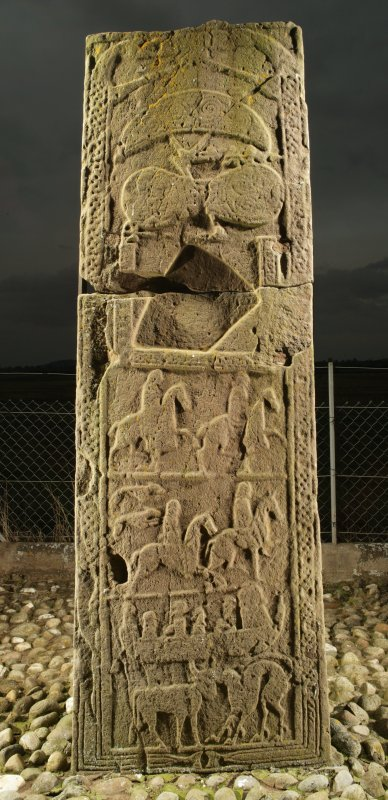 View of rear face of slab with pictish carvings including horsemen, men in boat, crescent and V rod and double disc and Z rod